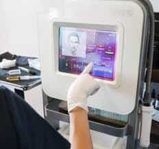 image of hand pointing at touchscreen of vivace microneedling electronic console